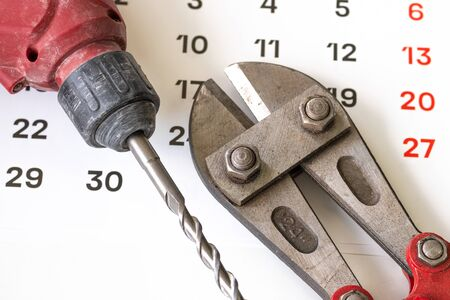 unclean dirty tools, drill and scissors for snacking wire on the calendar. scheduled installation work on a certain date