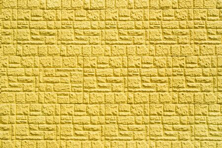 texture of yellow decorative brick in the form of tiles on the wall