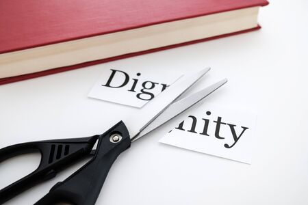 next to the book to be a pair of scissors and the word dignity is split into two parts. deleting a word from a book