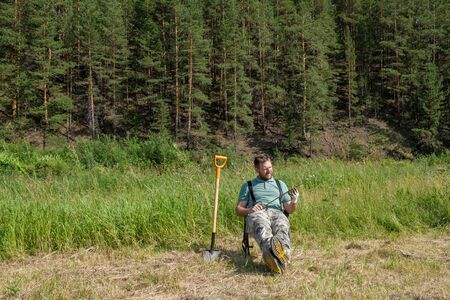 a man sits on a chair in a field against the background of a coniferous forest in his hand holding a machete next to a shovel stuck in the ground. the bandit killed and buried the victim is resting