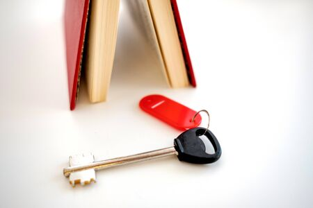 a large key with a red tag on a white background is located near the red book. key to a book or house