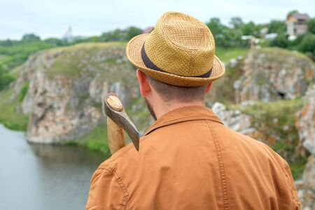 a man in a hat in a brown jacket with an axe on his shoulder background of a rock and a river. robber by the river Imagens