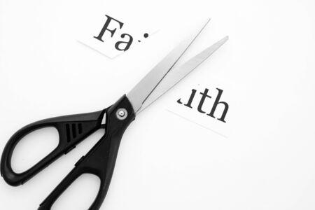 black stationery scissors cut faith written on paper