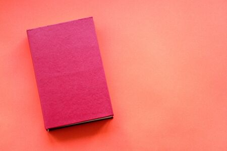 top view of a red closed book lying on a red paper background. similarity of color scheme