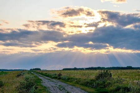 the sun's rays break through the heavy clouds at the time of sunset, the field road stretching into the distance and the tragic sky. alarming times in the sun will shine soon