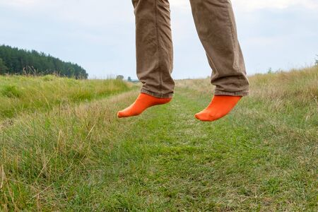 legs in orange socks while jumping on the background of a field road covered with grass. feet off the ground