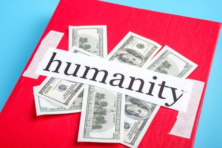 money is placed under the inscription humanity on the red book. everything is for money in our society