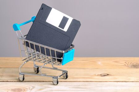 Old floppy disk in supermarket cart. old technology Фото со стока