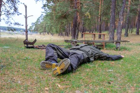 a man is lying in the forest near an extinct fire. an accident during a picnic in the countryside