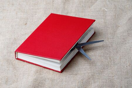 scissors stick out from the red book lying on the fabric. the book may hurt