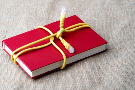 the red book is tied with a yellow internet cable. Internet closes books