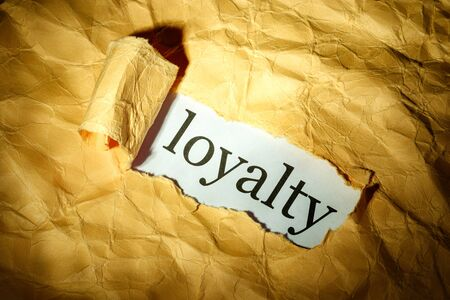 Loyalty inscription is visible through the hole on the lit paper with torn sides. loyalty search