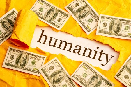 the inscription humanity is seen through torn orange paper around the scattered money. humanity and money
