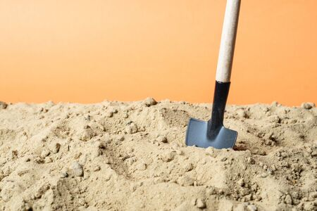 shovel stuck in the sand on an orange background. tool