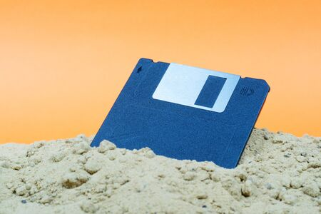 An old black floppy disk is half covered in sand. forgotten discarded technology