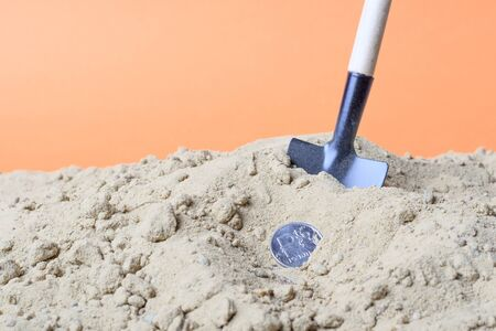 metal coin Russian ruble and a shovel in the sand. bury the ruble in the sand