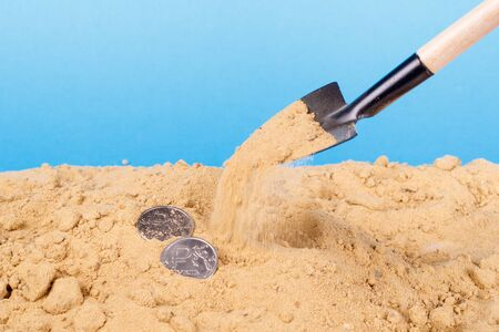 Close-up of a shovel throws sand coins over blue background. sand pour money Stok Fotoğraf