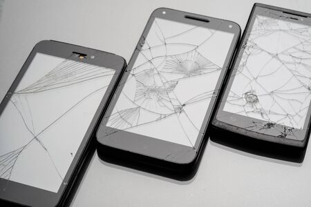 Three smartphones whose screens are broken and cracked. glareless background on broken glass
