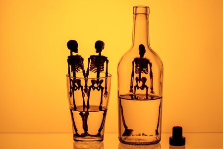silhouettes of skeletons in bottles on a yellow background. harm from drinking alcohol