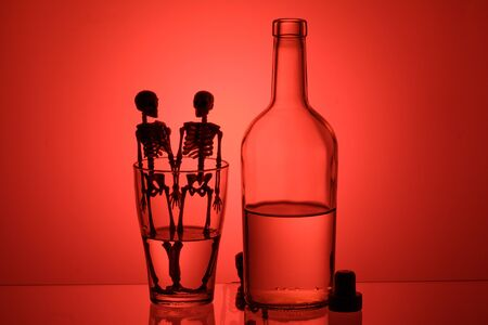 a bottle with liquid on a pink background next to a glass in it are glued together. who drinks a lot will die soon