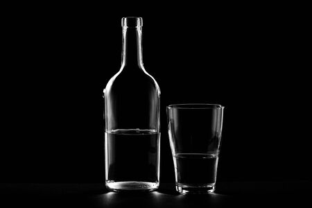 on a dark background, the bottle and glass are outlined. glare on the walls of the bottle and drinking tank 스톡 콘텐츠