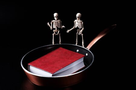 two skeletons on a dark background are discussing a red book lying on a frying pan. forbidden books go to hell
