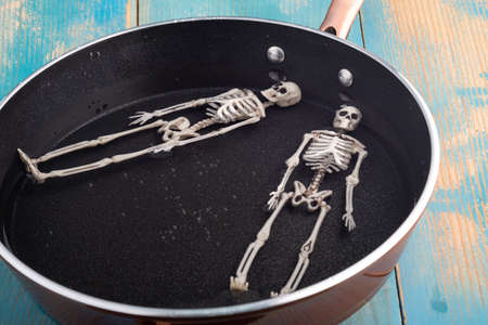 two skeletons rest lying on a pan with water in which there are bubbles. rest in hell