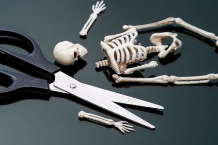 fragmented human skeleton on a black surface and scissors. cut a boring skeleton Stok Fotoğraf