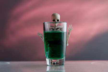 a stack with green liquid due to which a skeleton peeks out, the background is blurred. poison in a glass and death