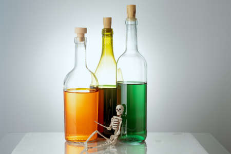 the skeleton lies on the background of three bottles with different liquids. alcohol harm concept 版權商用圖片