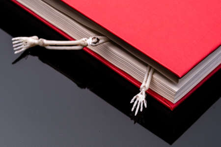 parts of the human skeleton crawling out of a closed red book. horrible mystery books 版權商用圖片