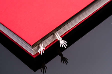 two hands of a human skeleton stick out from a closed red book. scary secrets secrets books 版權商用圖片