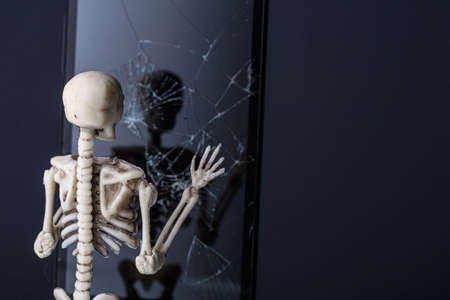 the human skeleton looks in a dark mirror with cracks. the deceased looks at himself