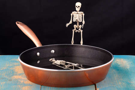 there's a human skeleton in the pan, and another skeleton above it. bathing evil spirits