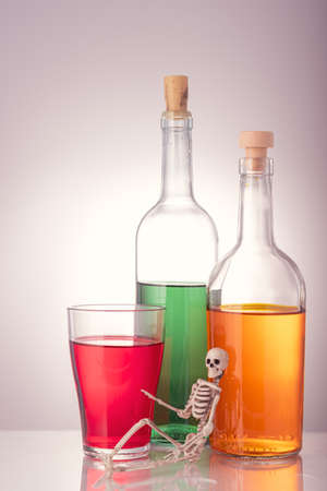 the skeleton is on the background of three bottles with various alcoholic drinks on a gray background. concept alcohol dangerous for life death awaits 版權商用圖片