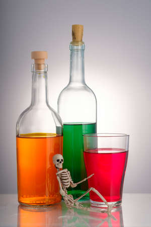 the skeleton is on the background of three bottles with various alcoholic drinks. hazardous drinks unhealthy 版權商用圖片