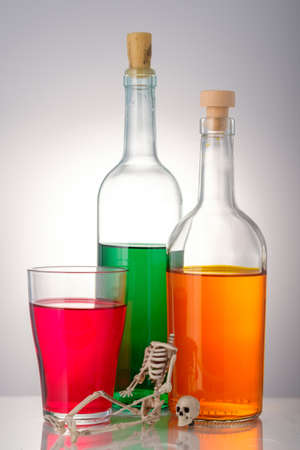 a skeleton without a head sits on the background of bottles of alcohol. concept of harm from drinking alcohol 版權商用圖片