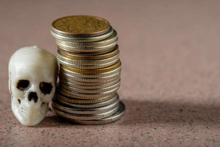a skull from a human skeleton and a stack of metal coins. deadly wealth 版權商用圖片