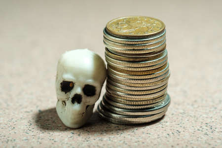skull from the human skeleton and a stack of coins. crisis in savings default