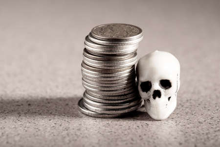 metal coins piled in a stack and a human skull. wealth endangering health