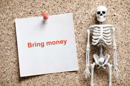 a skeleton on the wall next to it is a piece of paper on which is written back the debt. debt collector intimidation 版權商用圖片