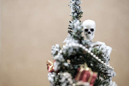 the skeleton is looking at us from the background in the foreground a small Christmas tree out of focus. the threat of New Years holidays because of the danger of death