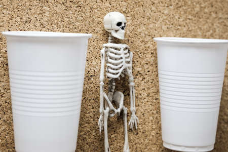 plastic container and plastic toy skeleton on a cork background. mortal danger of plastic and environmental pollution