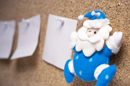 toy Santa Claus in blue and a to-do list next to him. Christmas things to whom to present