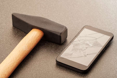 steel hammer and smartphone with a broken screen on a ceramic surface. hard and brittle 版權商用圖片