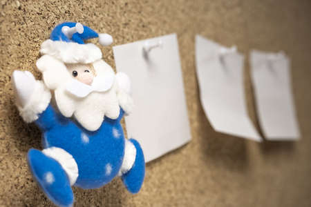 toy Santa Claus on a cork surface next to him stickers for reminder. christmas to-do list
