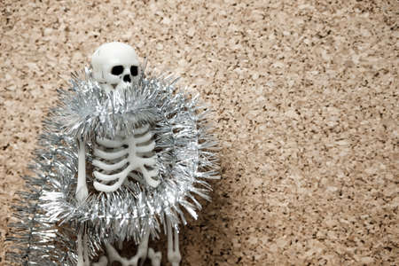 the human skeleton is wrapped with shiny New Year's decoration on the left of it is the free surface of a beige flower. holiday and events there will be no epidemic