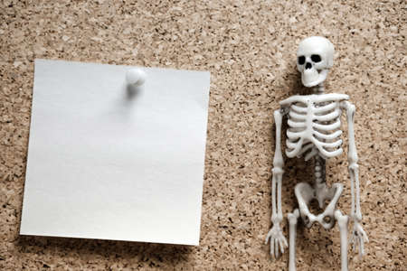 the human skeleton in the right corner of the frame on the left is blank note paper attached to a cork pin background. to report a bad or not happy event Stock fotó