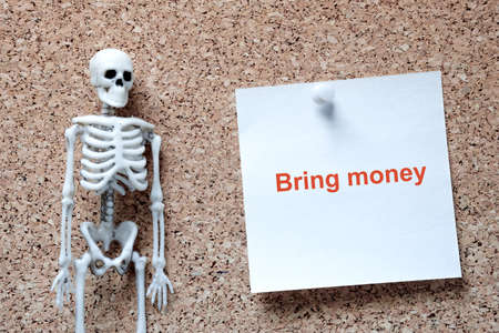 the human skeleton in the left corner of the frame on the right is blank note paper attached to a cork background on a pin. to report a bad or not happy event