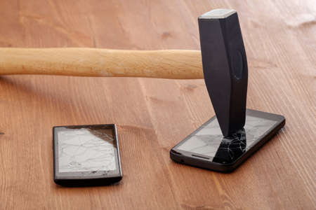 the hammer broke the screens of two smartphones on a wooden table. family disconnection from mobile slavery